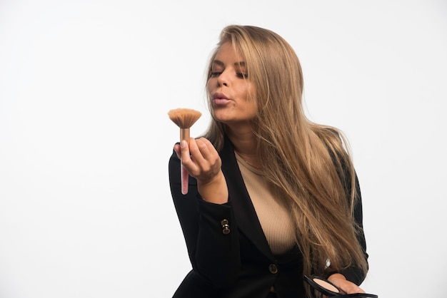 Jonge zakenvrouw in zwart pak blaast haar make-up borstel.