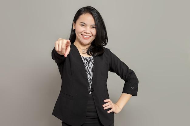 Jonge zakenvrouw in zwart pak die vooruit wijst met een glimlach