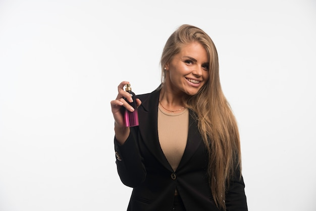 Jonge zakenvrouw in zwart pak geldt parfum en glimlacht.