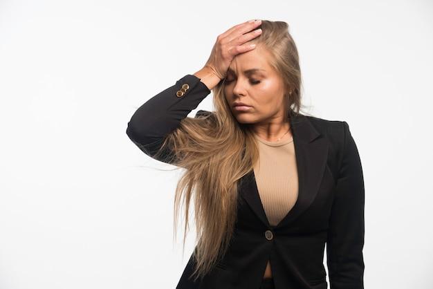 Jonge zakenvrouw in zwart pak haar hoofd zetten en ziet er moe uit.