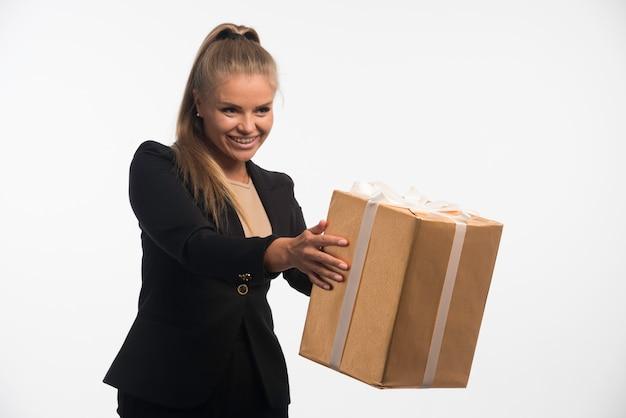 Jonge zakenvrouw in zwart pak kijkt naar een geschenkdoos en het vangen ervan.