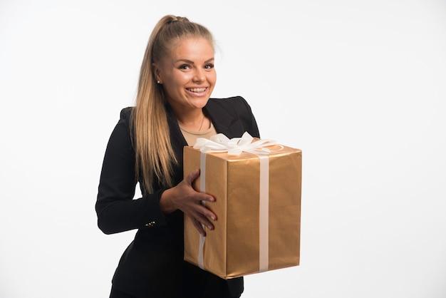 Jonge zakenvrouw in zwart pak kijkt naar een geschenkdoos en ziet er opgewonden uit