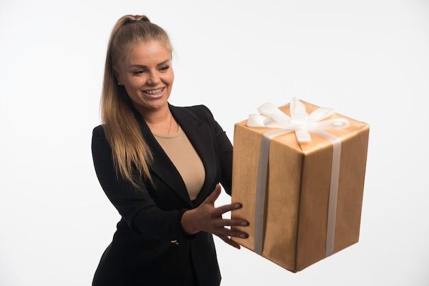 Jonge zakenvrouw in zwart pak kijkt naar een geschenkdoos.
