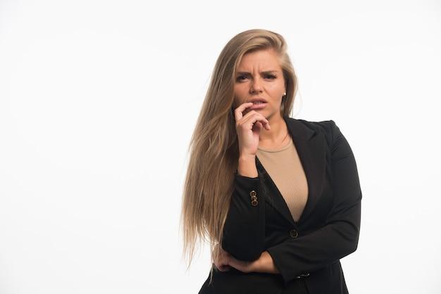 Jonge zakenvrouw in zwart pak kijkt verward met vinger naar haar mond.