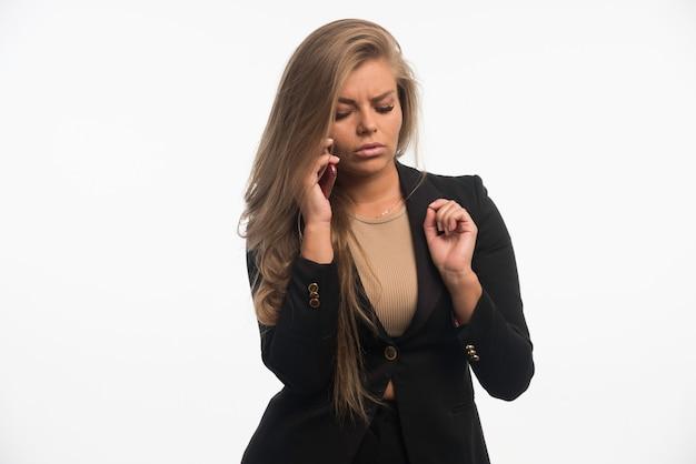 Jonge zakenvrouw in zwart pak lijkt twijfelachtig tijdens het gesprek met de telefoon.