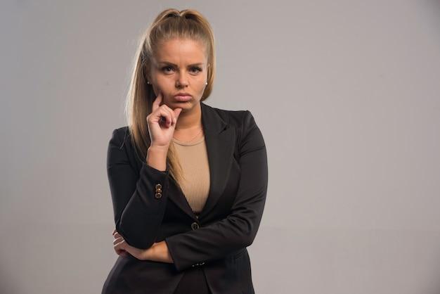 Jonge zakenvrouw in zwart pak lijkt twijfelachtig.