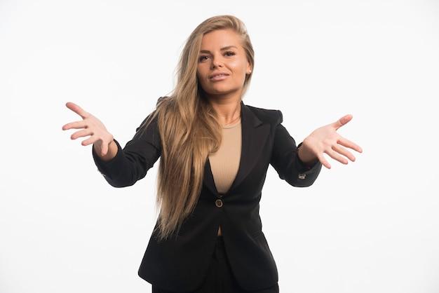 Jonge zakenvrouw in zwart pak maakt presentatie met handgebaren.