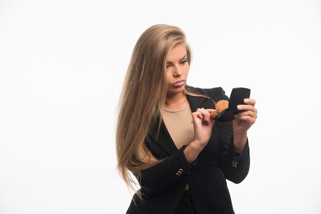 Jonge zakenvrouw in zwart pak make-up toe te passen en spiegel te gebruiken