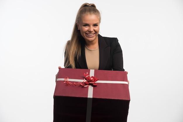 Jonge zakenvrouw in zwart pak met een grote geschenkdoos en glimlachen.