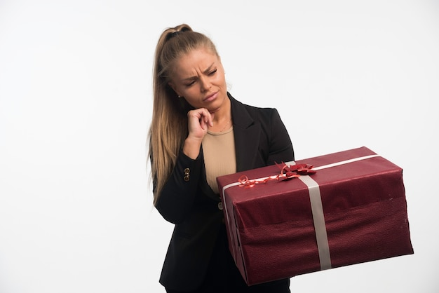Jonge zakenvrouw in zwart pak met een grote geschenkdoos en ziet er twijfelachtig uit.
