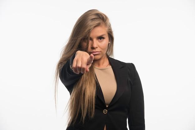 Jonge zakenvrouw in zwart pak naar voren gericht.