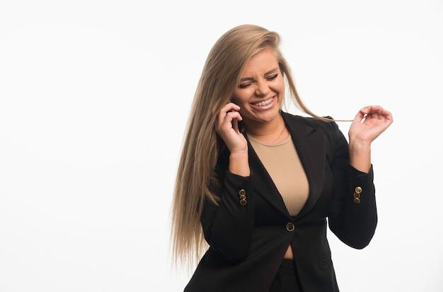Jonge zakenvrouw in zwart pak praten met de telefoon en glimlachen.