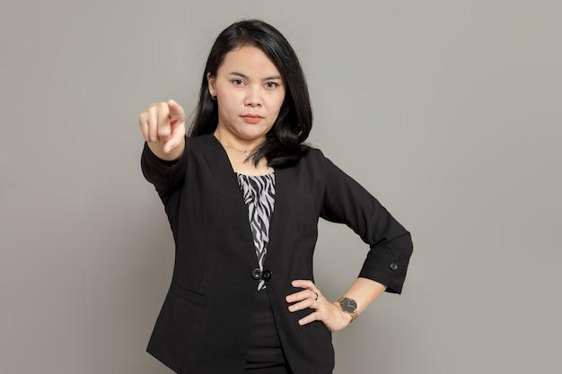 Jonge zakenvrouw in zwart pak wijst vooruit met serieuze gezichtsuitdrukking