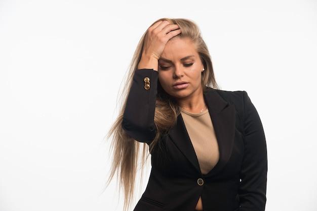 Jonge zakenvrouw in zwart pak ziet er aantrekkelijk en verleidelijk uit.