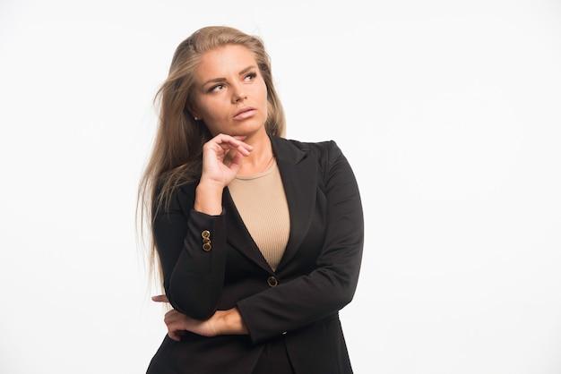 Jonge zakenvrouw in zwart pak ziet er attent uit.