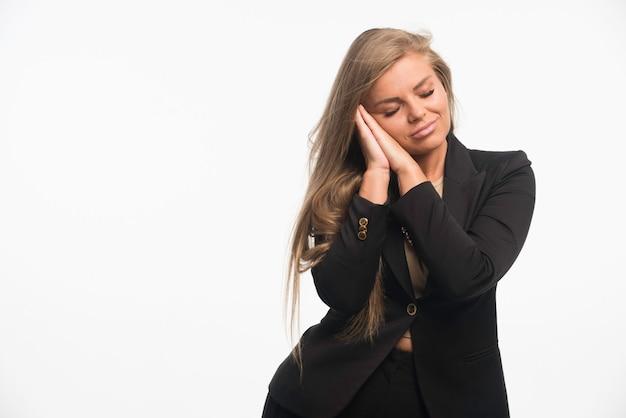 Jonge zakenvrouw in zwart pak ziet er dromerig uit