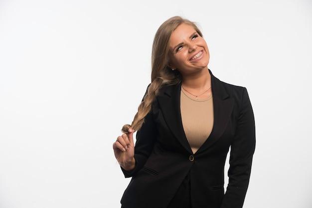 Jonge zakenvrouw in zwart pak ziet er gelukkig en glimlachend uit.