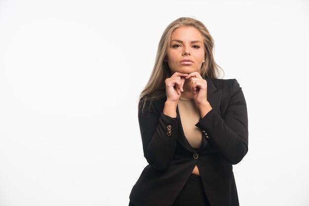 Jonge zakenvrouw in zwart pak ziet er toegewijd uit.