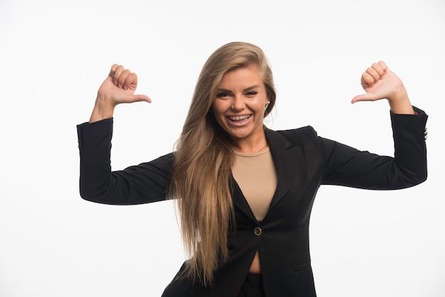 Jonge zakenvrouw in zwart pak ziet er zelfverzekerd uit en wijst zichzelf terwijl ze glimlacht
