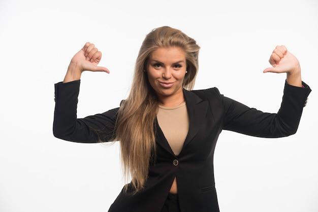Jonge zakenvrouw in zwart pak ziet er zelfverzekerd uit en wijst zichzelf.