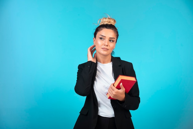Jonge zakenvrouw in zwarte blazer met een taakboek.