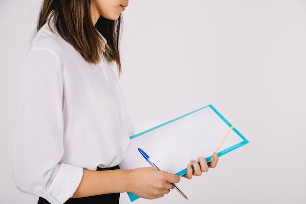 Jonge zakenvrouw kijken naar klembord