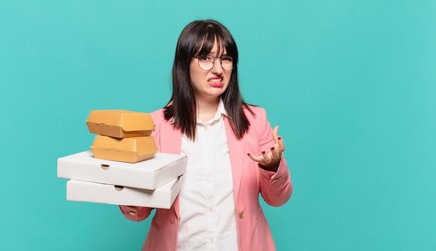 Jonge zakenvrouw kijkt boos, geïrriteerd en gefrustreerd schreeuwend wtf of wat is er mis met je?