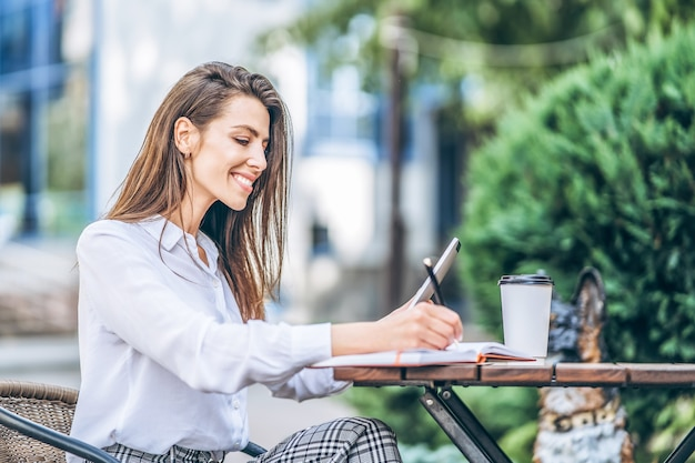 Jonge zakenvrouw koffie drinken en werken op tablet in straat café.
