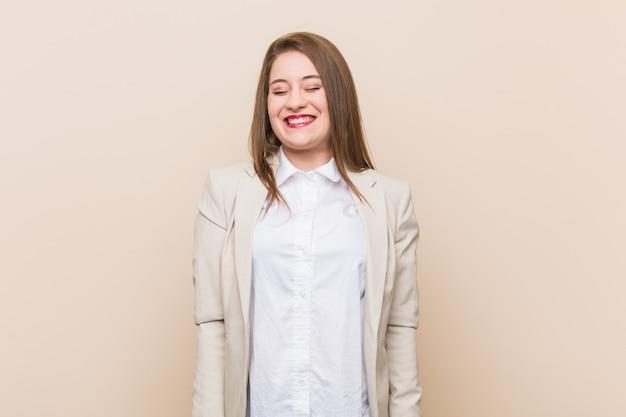 Jonge zakenvrouw lacht en sluit de ogen, voelt zich ontspannen en gelukkig.
