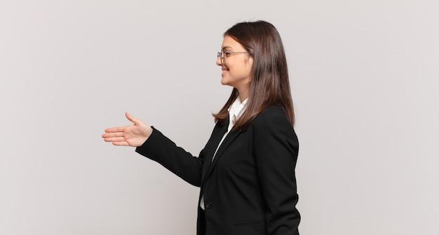 Jonge zakenvrouw lacht, groet je en biedt een handdruk om een succesvolle deal te sluiten, samenwerkingsconcept