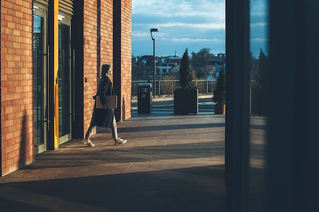 Jonge zakenvrouw loopt buiten met een laptop na het beëindigen van een werkdag