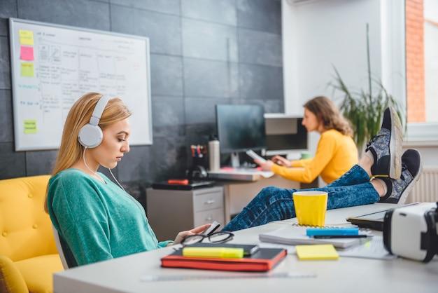 Jonge zakenvrouw luisteren muziek op kantoor