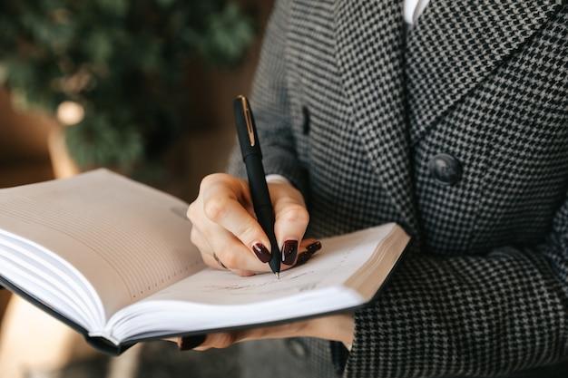 Jonge zakenvrouw maakt aantekeningen in een notitieblok op kantoor.