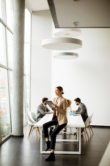 Jonge zakenvrouw met behulp van digitale tablet voor haar team in een modern kantoor