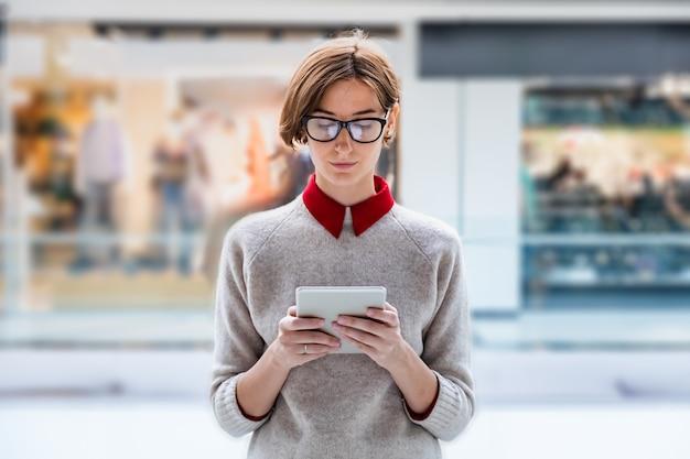 Jonge zakenvrouw met behulp van een tablet in een winkelcentrum. vrouwelijke persoon in slimme vrijetijdskleding in warenhuis dat met technologie werkt