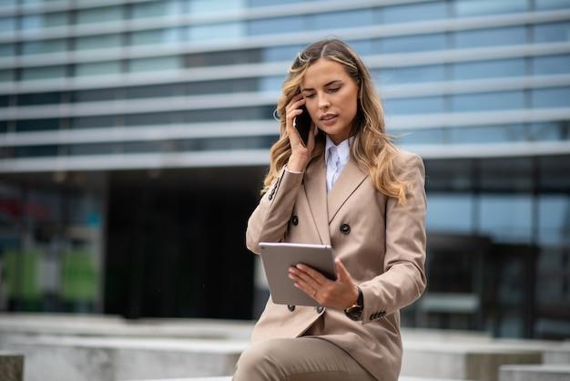 Jonge zakenvrouw met behulp van haar mobiele telefoon terwijl ze een tablet buiten houdt