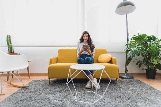 Jonge zakenvrouw met behulp van haar tablet zittend op de bank