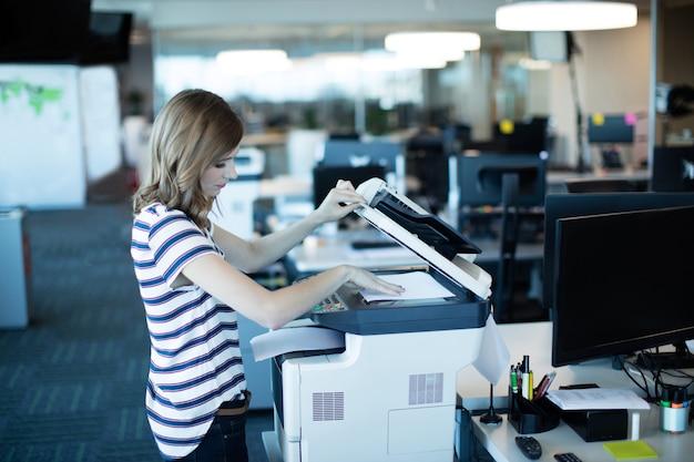 Jonge zakenvrouw met behulp van kopieermachine in kantoor Premium Foto