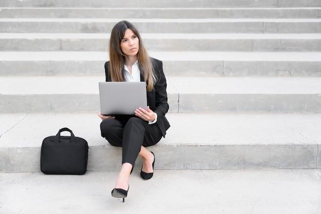 Jonge zakenvrouw met behulp van laptopcomputer in de stad