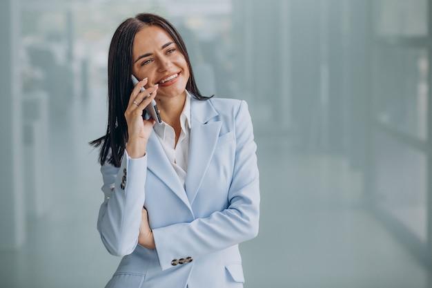 Jonge zakenvrouw met behulp van mobiele telefoon