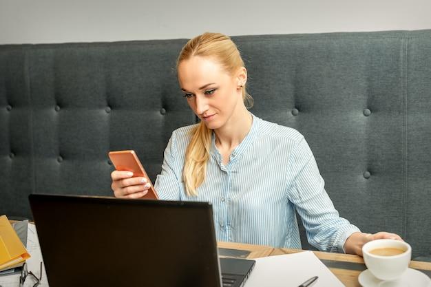 Jonge zakenvrouw met behulp van smartphone zittend aan tafel met laptop in café