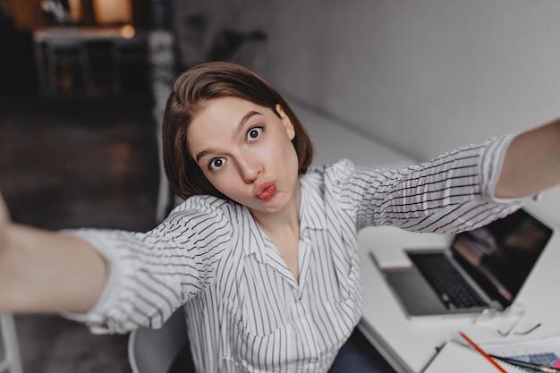 Jonge zakenvrouw met bruine ogen maakt selfie met grappige gezichtsuitdrukking tegen witte tafel en laptop.