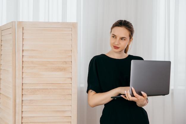 Jonge zakenvrouw met computer in haar handen in zwarte jurk in wit kantoor