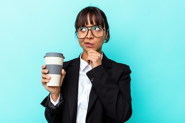 Jonge zakenvrouw met een gemengd ras die een koffie vasthoudt op een blauwe achtergrond die zijwaarts kijkt met een twijfelachtige en sceptische uitdrukking.