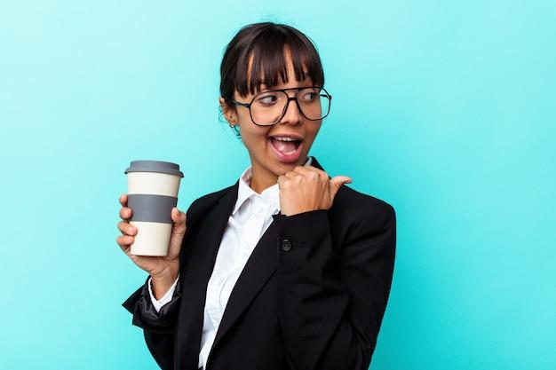 Jonge zakenvrouw met een gemengd ras die een kopje koffie vasthoudt op een blauwe achtergrond wijst met de duimvinger weg, lachend en zorgeloos.