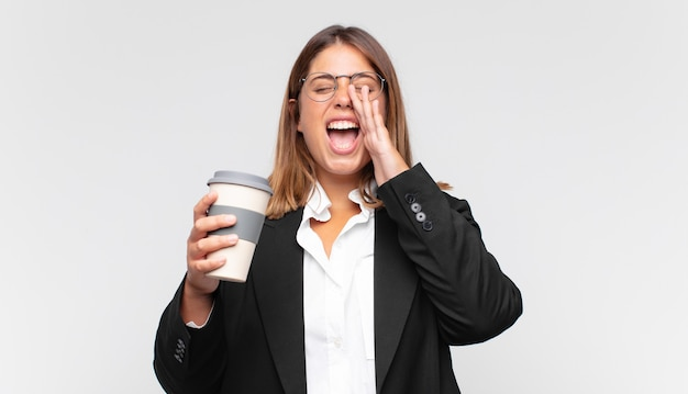 Jonge zakenvrouw met een koffie die blij, opgewonden en positief voelt, een grote schreeuw geeft