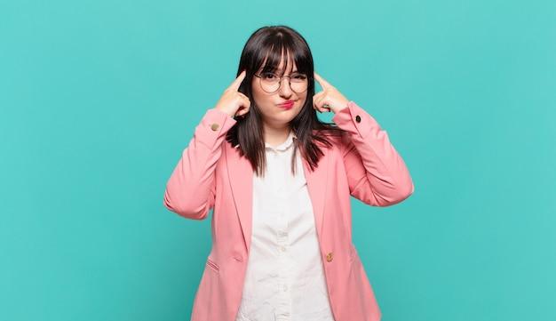 Jonge zakenvrouw met een serieuze en geconcentreerde blik, brainstormend en nadenkend over een uitdagend probleem