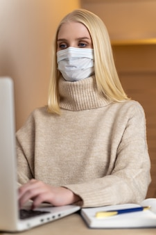 Jonge zakenvrouw met gezichtsmasker werkt op de computer zittend aan het bureau van de werkplek in kantoorruimte en beschermt zichzelf tegen het krijgen van grippe versus covid-19 coronavirus pandemie