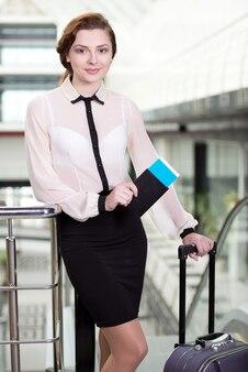Jonge zakenvrouw met koffer en vliegtuigtickets.