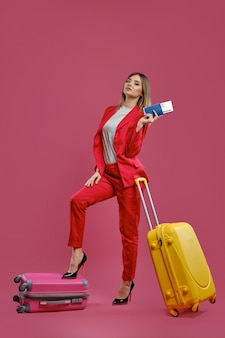 Jonge zakenvrouw met koffers, met paspoort en ticket. zakelijk reisconcept